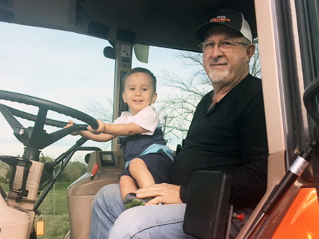 Andy and grandson in tractor cab