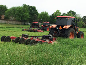 Three tractors mowing field-after